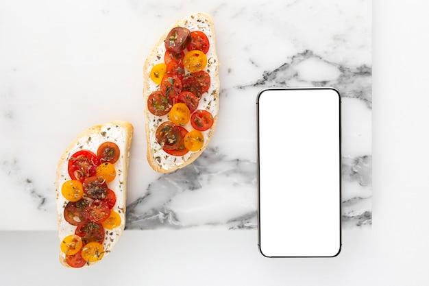 Vista dall'alto panino con crema di formaggio e pomodori con telefono vuoto