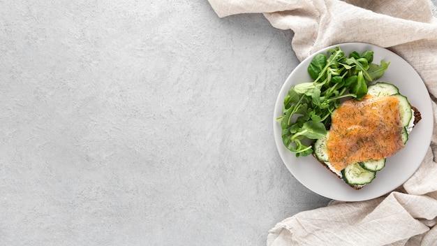 Vista dall'alto panino con cetrioli e salmone sul piatto con copia-spazio