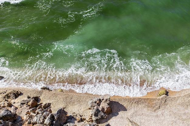 Vista dall'alto della costa del mare con acqua verde e surf su una spiaggia sabbiosa.