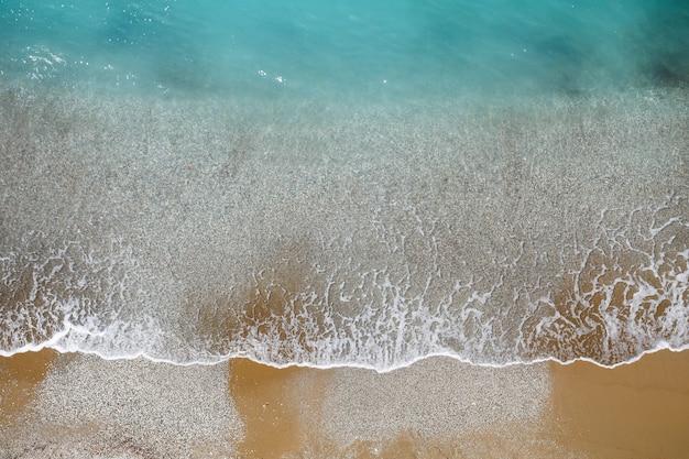 Vista dall'alto della riva del mare con acque azzurre e una spiaggia sabbiosa. vista aerea del mare della terra di mezzo con la costa. bellissimo mare tropicale nella stagione estiva, ripreso dal drone