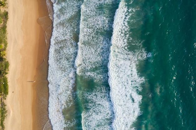 Vista dall'alto delle onde della trama del mare che schiumano e schizzano nell'oceano giornata di sole bellissimo sfondo della superficie del mare.