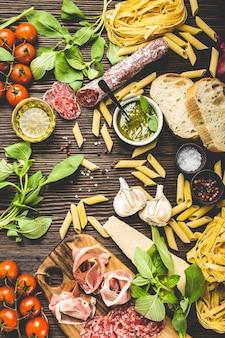 Vista dall'alto della selezione di cibo tradizionale italiano, antipasti e snack come salame, prosciutto, formaggio, pesto, ciabatta, olio d'oliva, pasta su fondo di legno rustico