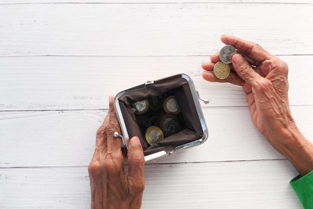 Vista dall'alto delle donne anziane mano risparmio di monete in una borsa