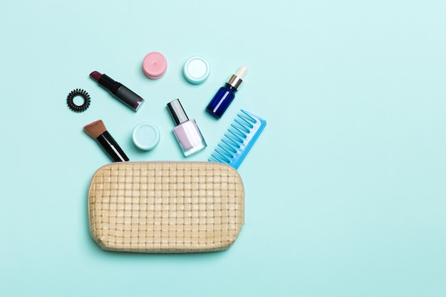 Vista dall'alto del set di prodotti per il trucco e la cura della pelle che fuoriescono dalla borsa dei cosmetici su sfondo blu. concetto di bellezza.