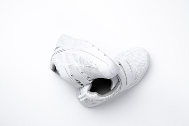 Set vista dall'alto di sneakers unisex bianche simbolo di sane abitudini sportive e salute isolate su uno sfondo bianco...