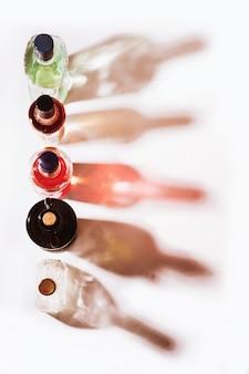 Vista dall'alto di diverse bottiglie di vetro colorate e le loro ombre in piedi su sfondo bianco