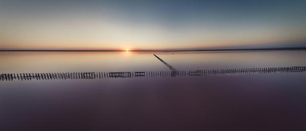 Vista dall'alto di un lago rosa salato lucido e un percorso lungo di esso
