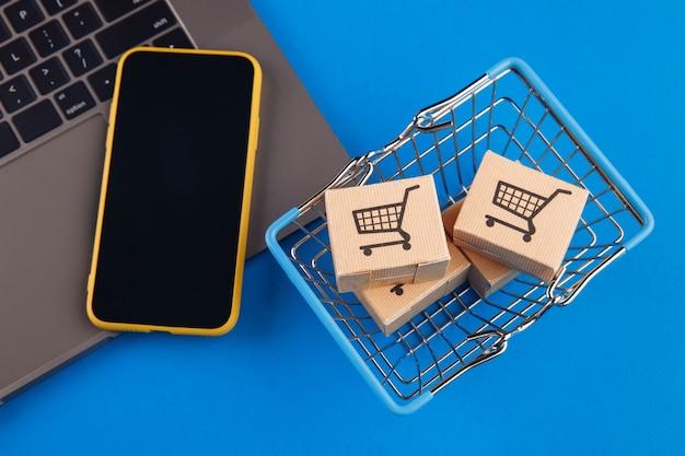 Vista dall'alto su un carrello della spesa, scatole e telefono cellulare su sfondo blu. concetto di acquisto online di smartphone