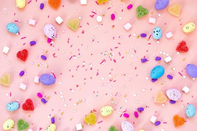 Colpo di vista superiore della decorazione di disposizione concetto felice del fondo di festa di pasqua. uova di coniglietto colorate piatte su una bella scrivania rosa. copia spazio.