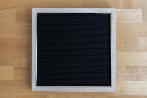Vista dall'alto di una tavola vuota nera su un tavolo di legno con copia spazio per le tue citazioni