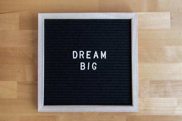 Vista dall'alto di una tavola vuota nera su un tavolo di legno con una grande citazione da sogno
