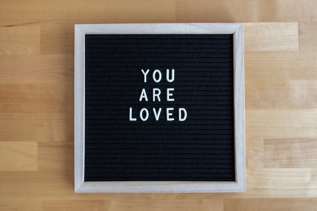 Vista dall'alto di una tavola vuota nera su un tavolo di legno con la tua citazione amata