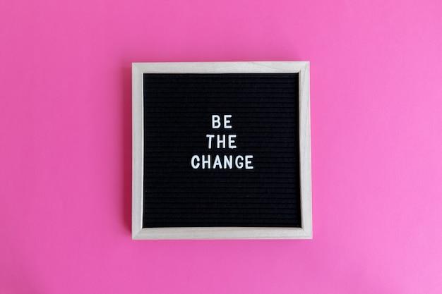 Vista dall'alto di una lavagna con una cornice bianca con un hashtag su uno sfondo rosa il cambiamento