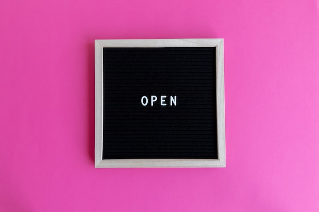 Vista dall'alto di una lavagna con una cornice di legno con un massaggio aperto su uno sfondo rosa