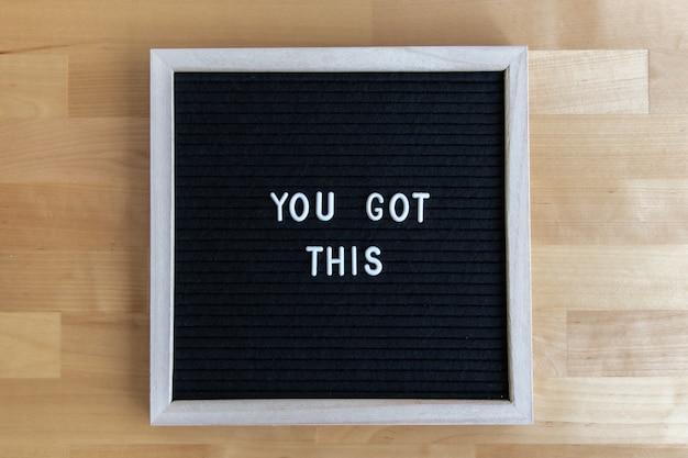Inquadratura dall'alto di una lavagna con te questa citazione su un tavolo di legno