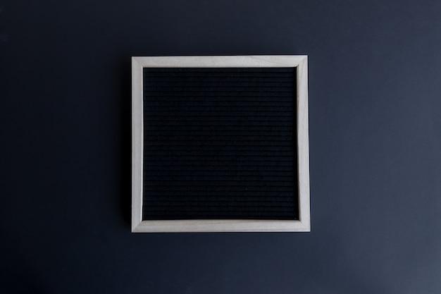 Vista dall'alto di una lavagna vuota con una cornice di legno su uno sfondo nero con spazio di copia