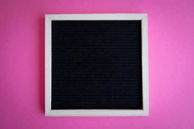 Vista dall'alto di una lavagna vuota con una cornice di legno su uno sfondo rosa con spazio per le copie