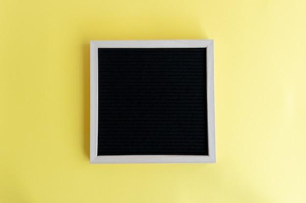 Vista dall'alto di una lavagna vuota con una cornice di legno su uno sfondo giallo con spazio di copia