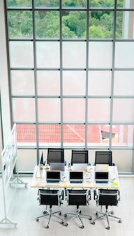 Vista dall'alto del tavolo della sala riunioni della conferenza in un ufficio aziendale vuoto pieno di computer portatili, tazze da caffè, documenti, documenti, sedie nere e pannello di vetro vicino alla costruzione di finestre di vetro.