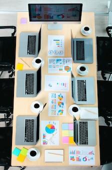 Vista dall'alto del tavolo della riunione della conferenza in una stanza vuota dell'ufficio aziendale piena di computer portatili caffè caldo nero in tazze bianche riportano dati documenti scartoffie post it e sedie nere.