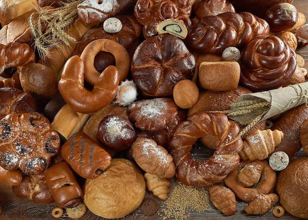 Vista dall'alto colpo di deliziosi panini dolci e diversi tipi di pane appena sfornato accatastati sul concetto di gastronomia di cottura del forno del copyspace del tavolo.
