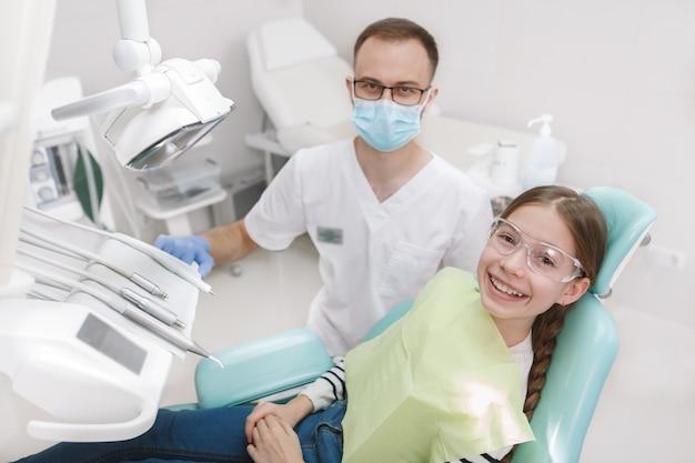 Colpo di vista dall'alto di un dentista al suo giovane paziente in poltrona odontoiatrica