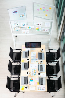 Vista dall'alto del tavolo di lavoro della sala riunioni in un ufficio aziendale vuoto pieno di computer portatili tazze da caffè report dati documenti documenti sedie nere e schermo monitor vuoto bordo di vetro vicino a finestre.
