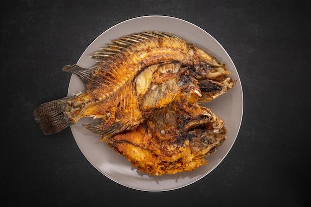 Vista dall'alto di gustoso pesce tilapia fritto di grandi dimensioni in piatto di ceramica su sfondo grigio scuro, grigio, nero