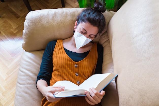 Vista superiore della maschera da portare d'uso della donna malata che legge un libro a casa. stare a casa. malattia da virus pandemico covida 19.
