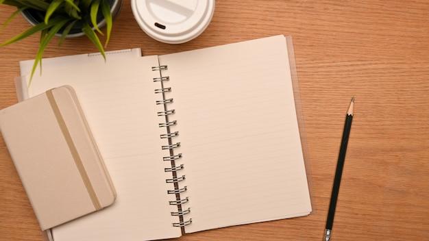Vista dall'alto della scrivania da studio semplice o della scrivania con pagine di quaderno vuote per montare il testo