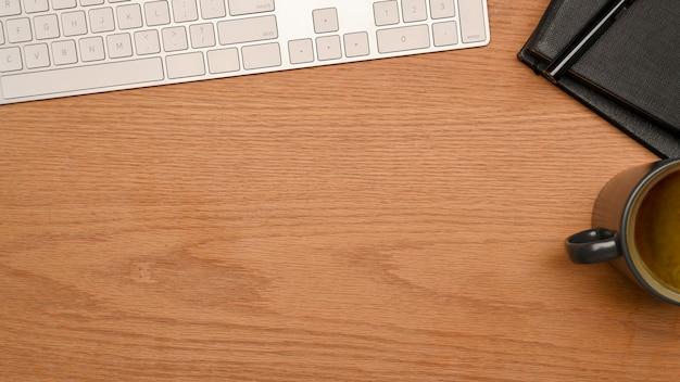 Vista dall'alto area di lavoro semplice con tastiera, tazza di caffè e spazio per il montaggio su tavolo di legno