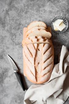 Vista dall'alto di pane a fette con coltello e burro