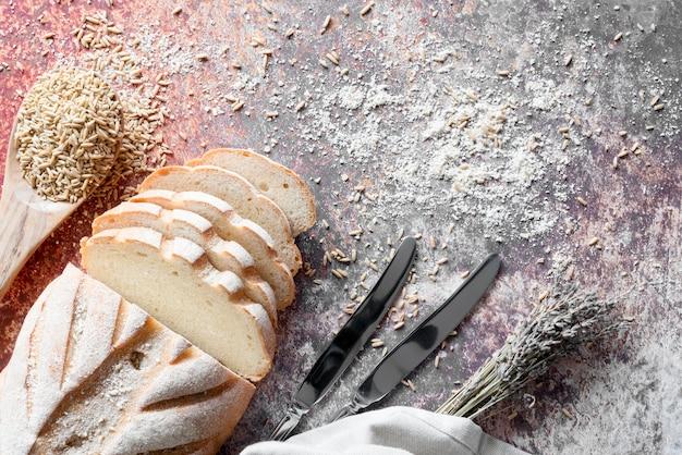 Vista dall'alto di pane a fette con coltelli