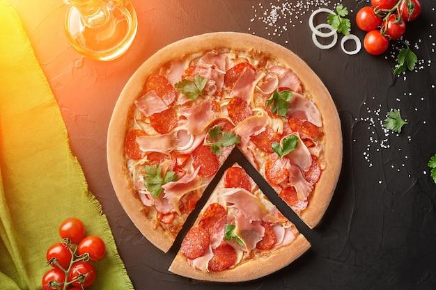 Vista dall'alto di pizza a fette con salame pancetta e prosciutto