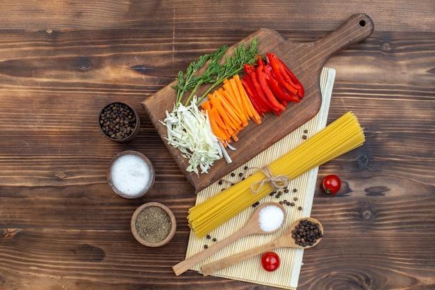 Vista dall'alto verdure a fette cavolo carota e pepe sulla superficie marrone del tagliere