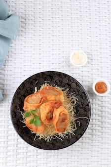 Vista dall'alto fette di involtini di uova di pollo, uova di frittata ripiene di pollo macinato e spezie, al vapore e fritte, servite con salsa maionese al peperoncino sopra i vermicelli croccanti