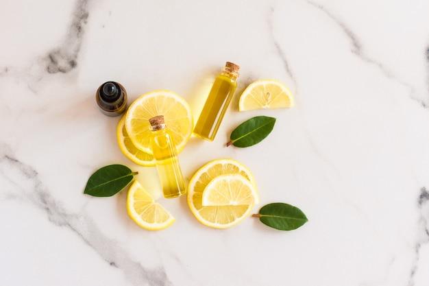 Vista dall'alto di fette di limone fresco, foglie di melissa e olio essenziale di sole luminoso in bottiglie di vetro con coperchio in sughero. prodotto cosmetico biologico naturale.