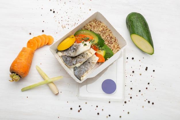 Vista dall'alto fette di pesce zucchine e porridge di frumento accanto a fette di porro e carota e condimenti. concetto di mangiare sano.