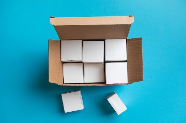 Vista dall'alto di una piccola scatola su sfondo blu.consegna o shopping online.comprare e vendere concetti