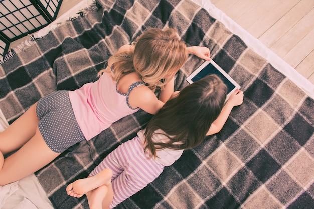 Vista dall'alto della piccola figlia e madre sdraiata sul letto con tablet
