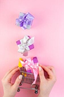 Vista dall'alto piccoli regali regalo nel carrello del piccolo mercato in mano femminile su sfondo rosa