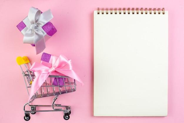 Vista dall'alto piccoli regali mini taccuino del carrello del mercato su sfondo rosa