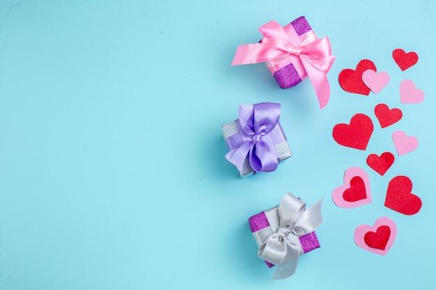 Vista dall'alto piccoli regali cuori rossi e rosa su sfondo blu con spazio libero