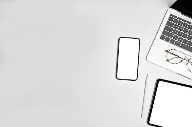 Smart phone, laptop, tablet digitale e occhiali vista dall'alto su sfondo bianco.
