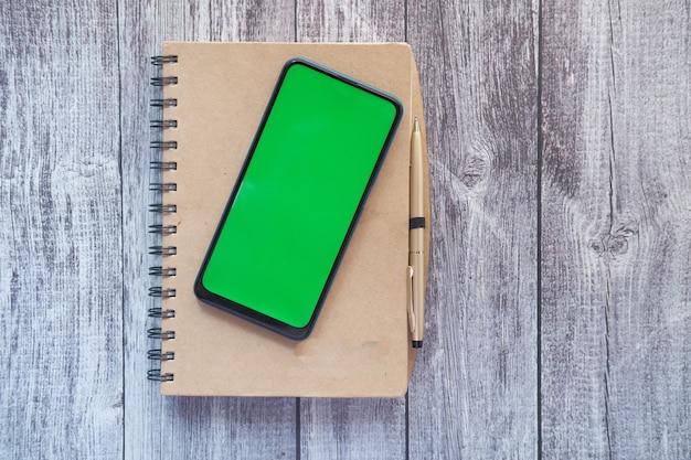 Vista dall'alto di smart phone e blocco note sul tavolo