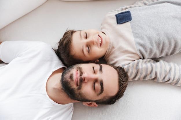 Vista dall'alto di un padre sorridente e suo figlio sdraiati su un divano a casa