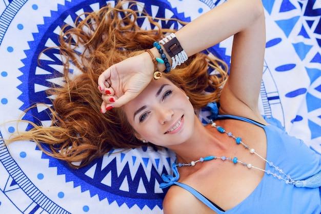 Vista dall'alto della donna sorridente che si distende sul telo da spiaggia nella soleggiata giornata estiva.
