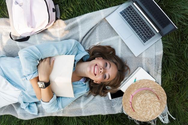 Vista dall'alto di una giovane ragazza adolescente sorridente posa su una coperta