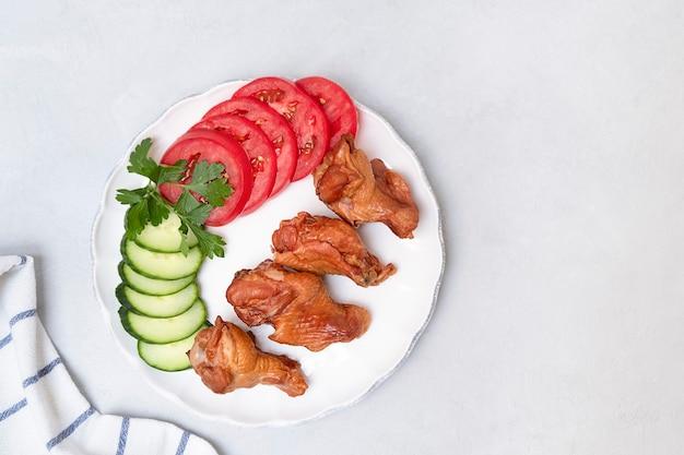 Vista dall'alto di ali affumicate con verdure fresche su piatto bianco su sfondo grigio neutro con spazio ...