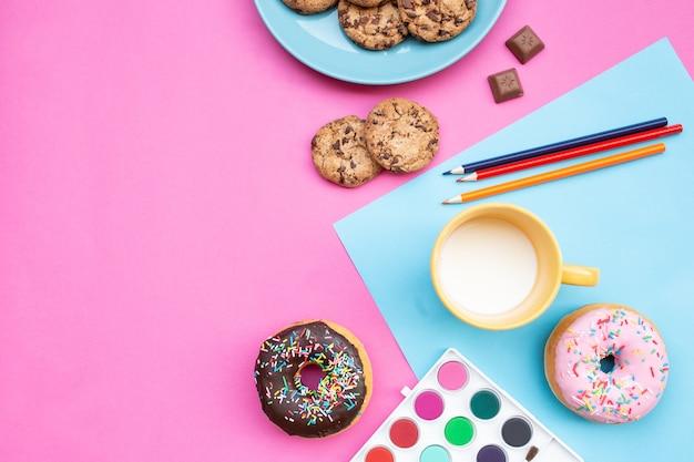 Vista dall'alto della merenda con biscotti biscotti, latte, once di cioccolato e ciambelle, con sfondo blu e rosa, matite colorate e scatola di acquerelli